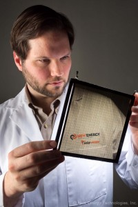 Dr. Scott Hammond, New Energy's Principal Scientist, Displays Neutral-Grey Tinted High-Performance SolarWindow™ Prototype.